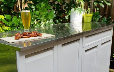 beer and wings on stainless countertop on rain day